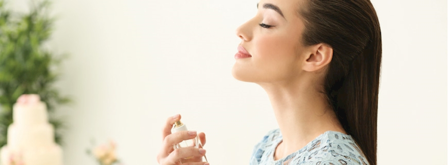 Person spraying perfume on themselves